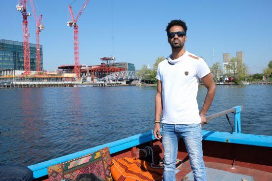 Geroutineerd leidt kapitein Sami het bootje door de grachten. Rondvaart door de Amsterdamse grachten met Rederij Lampedusa. Vluchtelingen vertellen tijdens de boottocht hun verhaal.