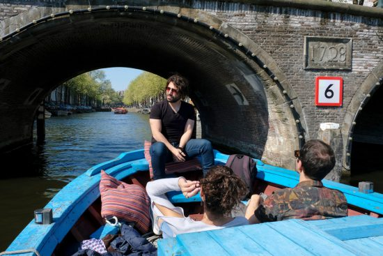 Storyteller Tommy en enkele gasten aan boord van boot Hedir. Rondvaart door de Amsterdamse grachten met Rederij Lampedusa. Vluchtelingen vertellen tijdens de boottocht hun verhaal.