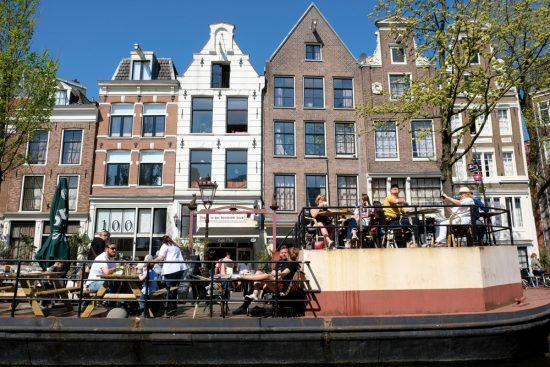 Genieten van het mooie weer langs de Amsterdamse grachten. Rondvaart door de Amsterdamse grachten met Rederij Lampedusa. Vluchtelingen vertellen tijdens de boottocht hun verhaal.