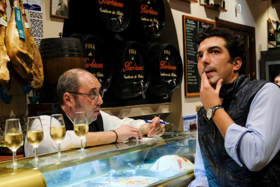 Gids Adolfo van Sevilla Ambassadors bedenkt welke tapas hij gaat bestellen. Stedentrip Sevilla, Spanje, Seville, city trip