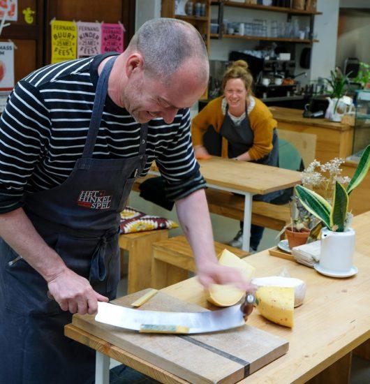 Filip van Het Hinkelspel snijdt de kaas in hapklare stukken. Sneukelen in Gent, stedentrip Belgie