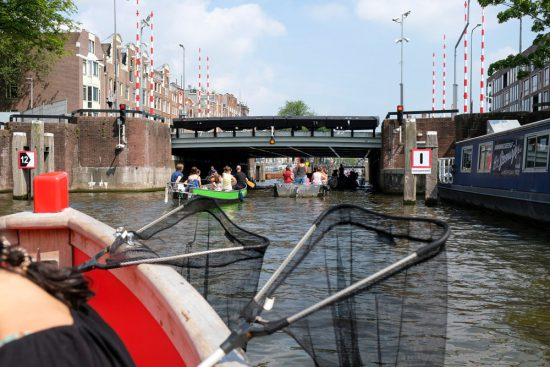 Even een rustmomentje als we wat sneller door Amsterdam varen. Plastic Whale vissen in de Amsterdamse grachten , de dag na Pride Amsterdam