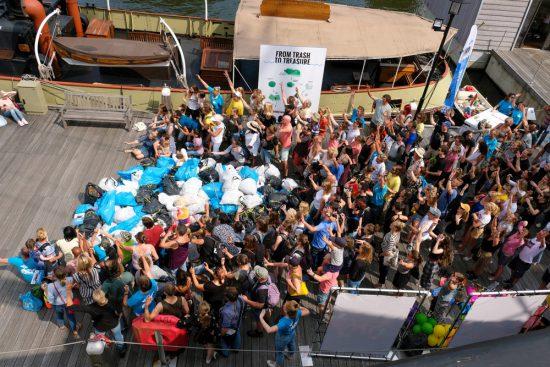 Een Plastic Whale groepsfoto met de afvalbuit van de dag. Plastic Whale vissen in de Amsterdamse grachten , de dag na Pride Amsterdam