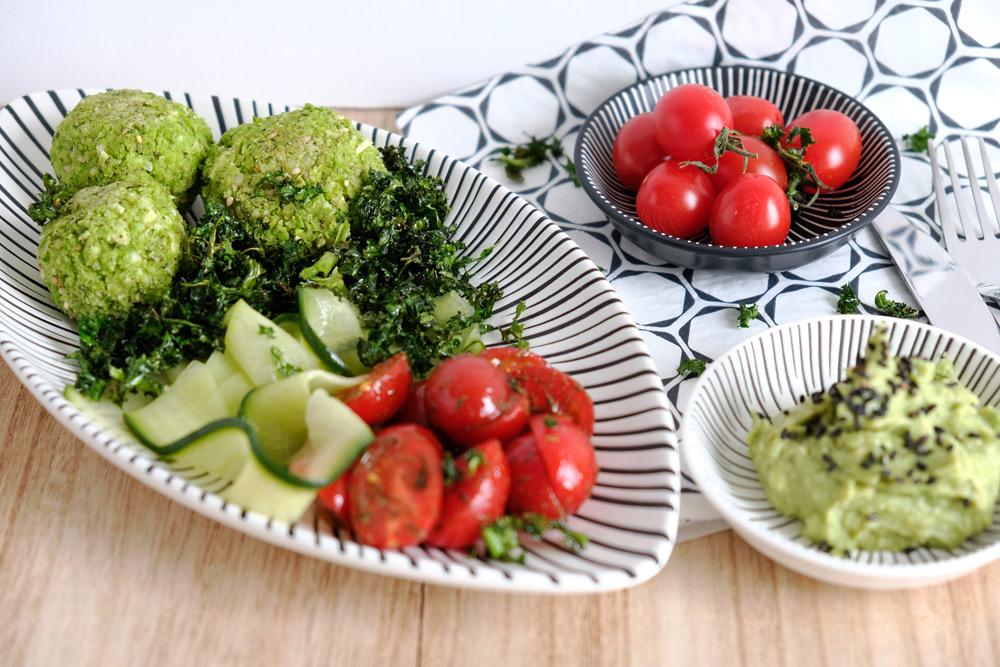 Salade met edamamefalafel, tomaat, komkommerlinten en krokante boerenkool. Met avocadospread