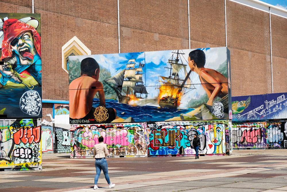 Op het NDSM-plein blijf je kijken naar de kunstwerken op muren en containers. Wandelroute Amsterdam-Noord, wandelen, duurzaam